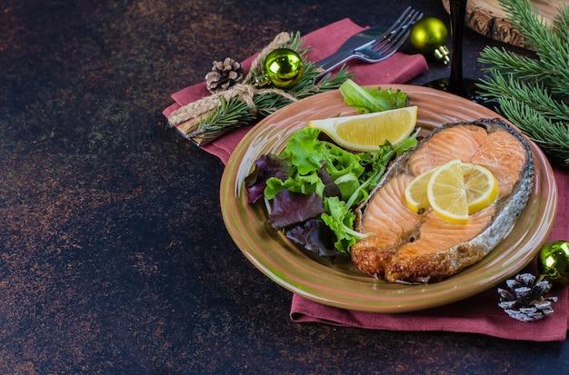 Świąteczne nakrycie stołu. pyszny stek z łososia z grilla na talerzu z cytryną i bukietem surówek na stole z ciemnego kamienia. widok z góry, kopia przestrzeń Premium Zdjęcia