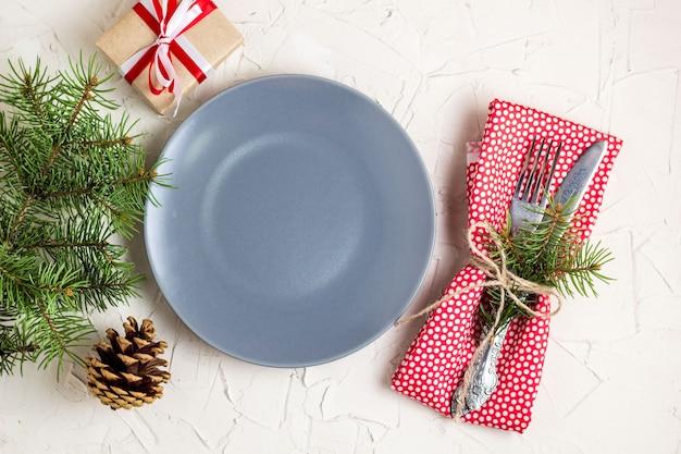 Świąteczne nakrycie stołu z prezentem szary talerz na białym stole. widok z góry koncepcja boże narodzenie Premium Zdjęcia