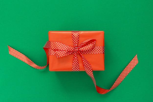 Świąteczne Tło Z Prezentem, Czerwone Pudełko Ze Wstążką W Kropki I Kokardą Na Zielonym Tle, Płaskie Lay, Widok Z Góry Premium Zdjęcia