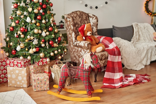 Świąteczne Wnętrze Sypialni Dziecięcej Boże Narodzenie W Pokoju Dziecinnym. Koń Na Biegunach I Miękkie Zabawki Opatrzone Na Tle Choinki. Premium Zdjęcia