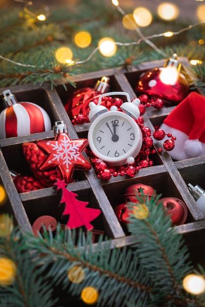 Świąteczne zabawki z czerwonego i białego szkła, budzik, czapka świętego mikołaja w koszu z gałęzi jodłowych Premium Zdjęcia