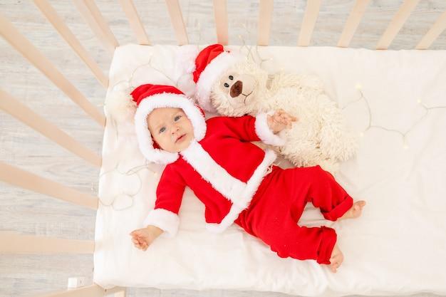 Świąteczne Zdjęcie Dziecka W Stroju świętego Mikołaja Leżącego W łóżeczku W Domu Z Zabawką W Czapce świętego Mikołaja Premium Zdjęcia
