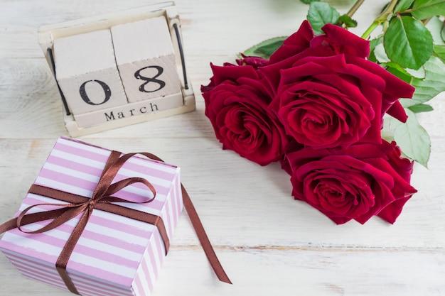 Świąteczny prezent, drewniany kalendarz, bukiet czerwonych róż i pudełko na drewnianym tle. koncepcja gratulacji 8 marca lub dnia woomana. Premium Zdjęcia