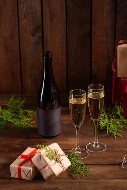 Świąteczny stół świąteczny z okularami, butelką i prezentami Premium Zdjęcia