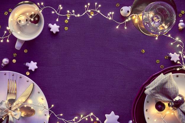 Świąteczny Stół Z Białym Talerzem I Złotymi Naczyniami Oraz Pozłacanymi Dekoracjami. Rozłożony Na Płasko, Widok Z Góry Na Ciemnej Lnianej Tkaninie Premium Zdjęcia