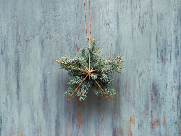 Świąteczny Wieniec W Kształcie Złotej Geometrycznej Gwiazdy Z Gałązkami Jodły Zawieszony Jest Na Rustykalnych Drewnianych Drzwiach, Tradycyjny Ornament świąteczny. Premium Zdjęcia