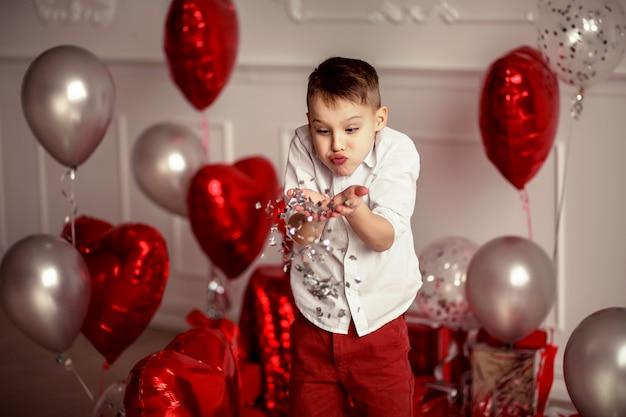 Świąteczny Wystrój Na Urodziny Lub Walentynki. Balony W Kształcie Dużych Czerwonych Serc I Konfetti. Wesoły Chłopiec Dziecko Wieje I Rzuca Konfetti Premium Zdjęcia