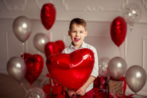Świąteczny Wystrój Na Urodziny Lub Walentynki. Przewiewne Szare Metaliczne Balony I Konfetti. Wesoły Dziecko Chłopiec Trzyma W Ręku Czerwony Balon W Kształcie Serca Premium Zdjęcia