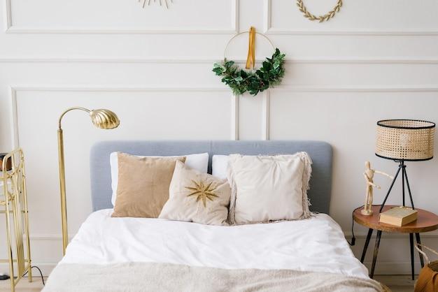 Świąteczny Wystrój W Sypialni. łóżko Z Poduszkami, Nad łóżkiem Wianek Premium Zdjęcia
