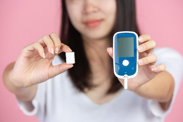 Światowy Dzień Cukrzycy; Kobieta Trzyma Glukometr I Kostki Cukru Na Różowej ścianie Darmowe Zdjęcia