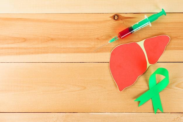 Światowy Dzień Zapalenia Wątroby. 28 Czerwca. Zielona Jade Taśma, Wątroba I Strzykawka Z Krwią Na Drewnianym Stole. Premium Zdjęcia