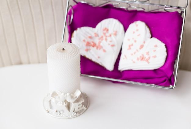 Świeca i ciastka w kształcie serca na różowej serwetce Premium Zdjęcia