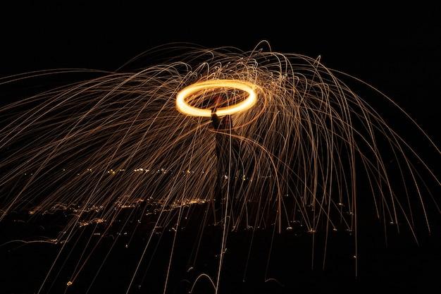 Świecące światło Wysyła Swoje Iskry W Powietrze, Gdy Szybko Się Obraca Darmowe Zdjęcia