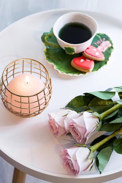 Świeczka Z Różowymi Różami I Filiżanką Herbata Na Bielu Stole Premium Zdjęcia