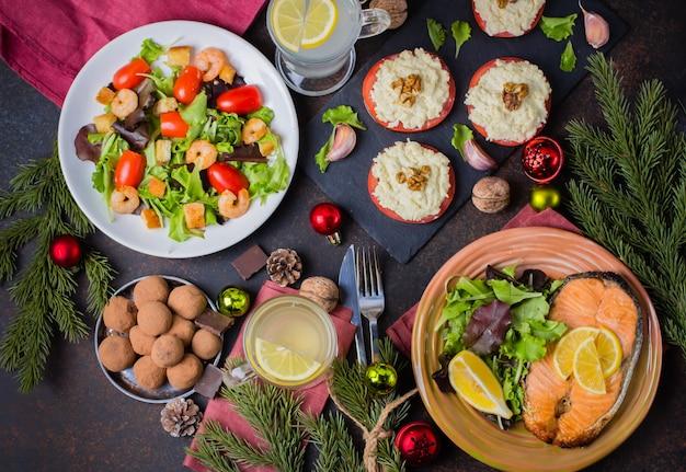 Święta bożego narodzenia lub nowy rok rodzinna koncepcja ustawienia stołu z dekoracją świąteczną. pyszny pieczony stek łosoś, sałatka, przekąski i deser na kamiennym ciemnym stole. widok z góry Premium Zdjęcia