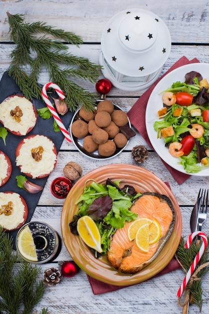 Święta bożego narodzenia lub nowy rok rodzinna koncepcja ustawienia stołu z dekoracją świąteczną. wyśmienicie pieczony stek łosoś, sałatka, przekąski i deser na biały drewniany. widok z góry Premium Zdjęcia