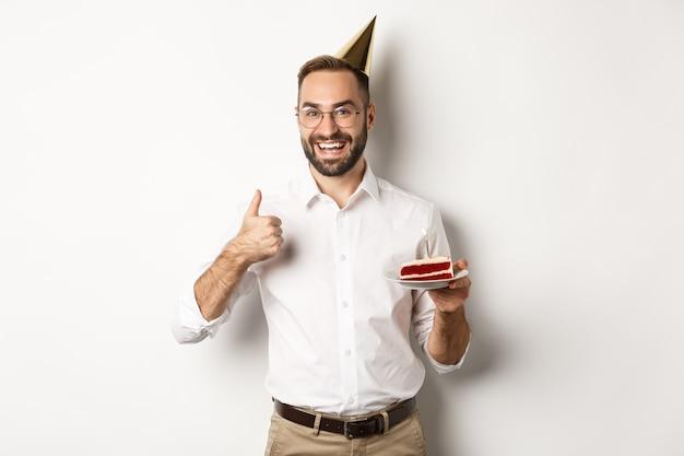 Święta I Uroczystości. Zadowolony Mężczyzna Korzystający Z Przyjęcia Urodzinowego, Trzymający Tort Urodzinowy I Pokazujący Kciuk W Górę Z Aprobatą, Polecający Coś, Białe Tło. Darmowe Zdjęcia