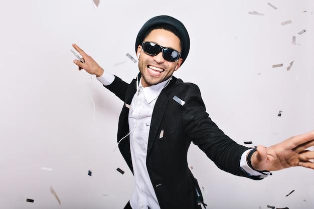 Świętujemy Imprezę Karaoke Podekscytowanego Przystojnego Faceta W Garniturze, Kapeluszu I Czarnych Okularach Przeciwsłonecznych, Bawiącego Się W świecidełkach. Modny Wygląd, śpiew, Tancerz, Szczęście, Wyrażenia, Muzyka, Radość. Darmowe Zdjęcia
