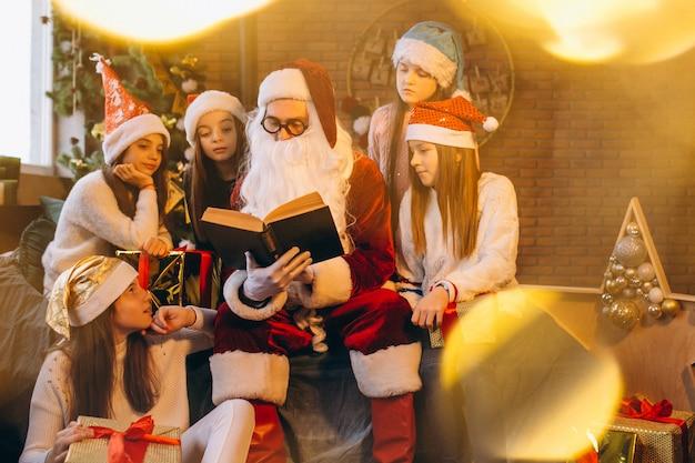 Święty mikołaj czyta książkę grupa dzieciaki Darmowe Zdjęcia