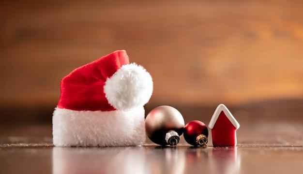 Święty Mikołaj Kapelusz I Mały Dom Na Drewnianym Stole Premium Zdjęcia