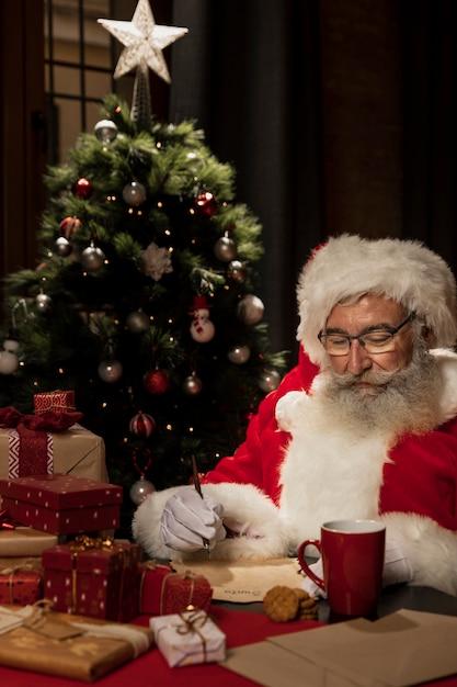 Święty mikołaj otoczony świątecznych prezentów Darmowe Zdjęcia