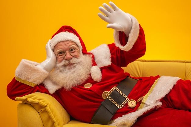 Święty Mikołaj Siedzi Na żółtej Kanapie Premium Zdjęcia