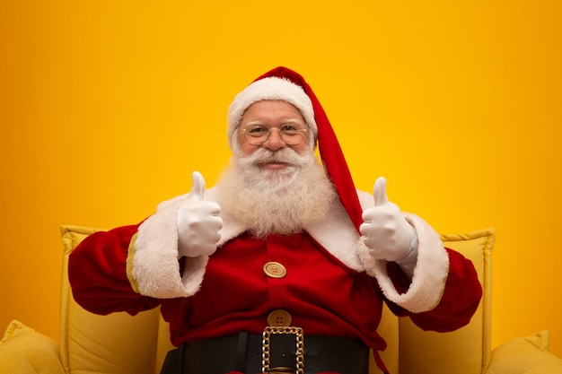 Święty Mikołaj Siedzi Na żółtej Leżance Na Kolorze żółtym Premium Zdjęcia