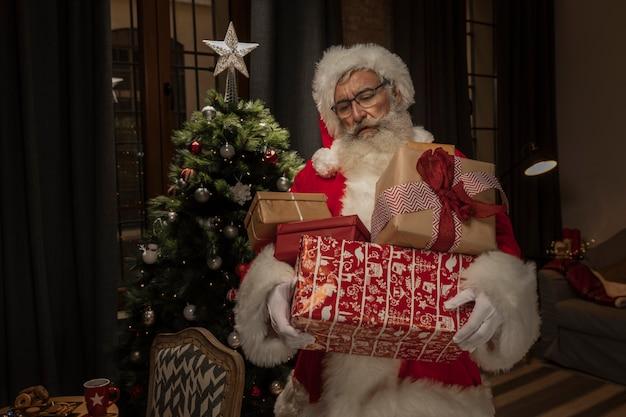 Święty mikołaj trzyma boże narodzenie teraźniejszość Darmowe Zdjęcia