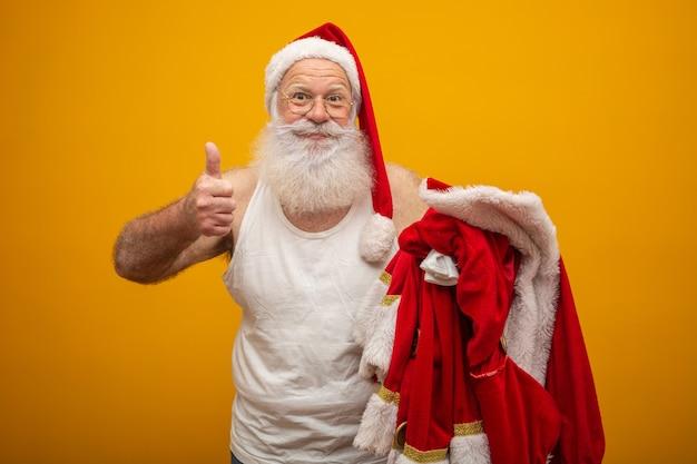 Święty mikołaj trzyma swoje ubrania przed lub przed dostarczeniem prezentów. Premium Zdjęcia