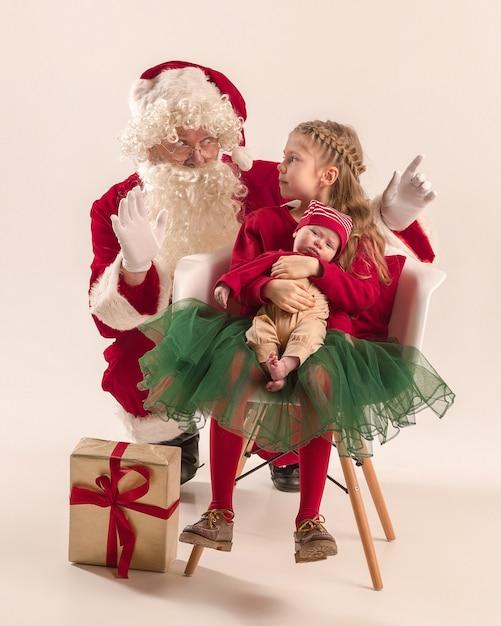 Święty Mikołaj W Czerwonym Stroju Z Małą Dziewczynką I Dzieckiem Na Białym Tle Darmowe Zdjęcia