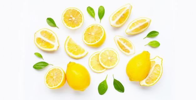 Świeża cytryna i plasterki z liśćmi odizolowywającymi na bielu. Premium Zdjęcia