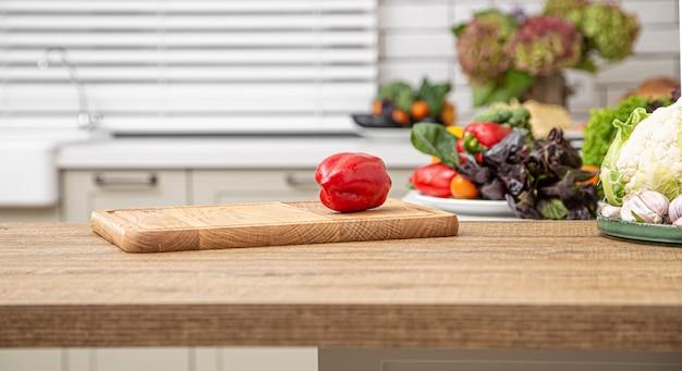 Świeża Czerwona Papryka Na Drewnianej Desce Na Tle Wnętrza Kuchni. Darmowe Zdjęcia