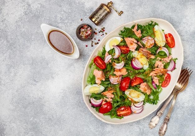 Świeża delikatesowa sałatka z łososia z sałatą, pomidorami, jajkami i czerwoną cebulą Premium Zdjęcia