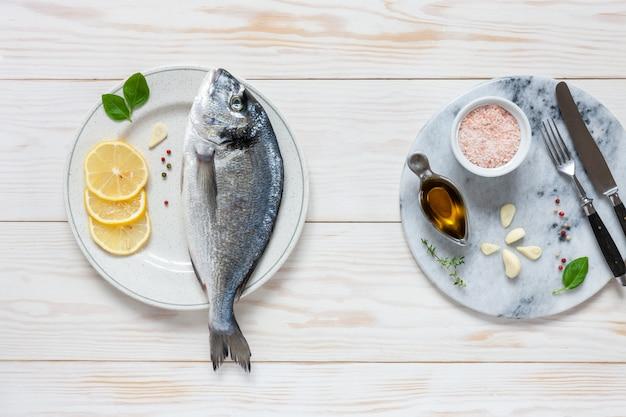 Świeża Dorado Ryba Z Pikantność, Oliwa Z Oliwek, Czosnkiem I Przyprawą Na Białym Naczyniu Na Bielu Stole. Premium Zdjęcia