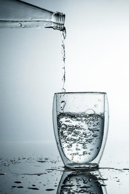 Świeżą I Zimną, Czystą Wodę Wlewa Się Do Szklanki. Oczyszczona Woda W Szklance Na Szarej ścianie. Motion Freeze Splash Kryształowej Wody Na Szarej ścianie. Premium Zdjęcia