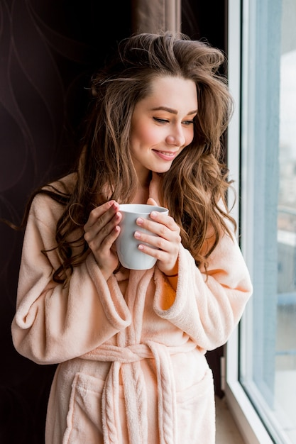 Świeża Młoda Kobieta W Różowym Szlafroku Przetargu Pić Herbatę, Patrząc Przez Okno. Darmowe Zdjęcia