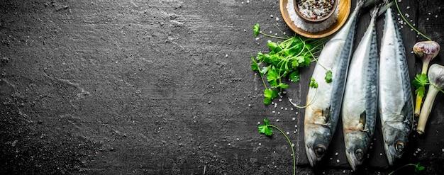 Świeża Surowa Makrela Na Kamieniu Deska Z Czosnkiem, Przyprawami I Ziołami. Na Czarnym Rustykalnym Stole Premium Zdjęcia