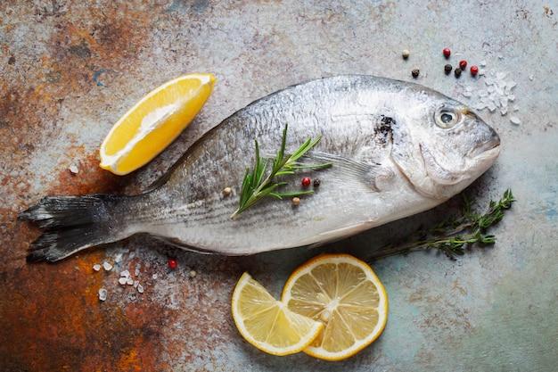Świeża surowa ryba dorado z przyprawami i oliwą z oliwek na błękitnym ośniedziałym stole. widok z góry. leżał płasko. Premium Zdjęcia