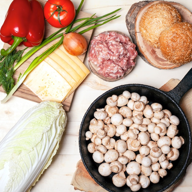 Świeża Surowa żywność Dla Hamburgerów, Bułek Szampinion Grzyby Warzywa I Mięso Płaskie Leżał Widok Z Góry. Premium Zdjęcia