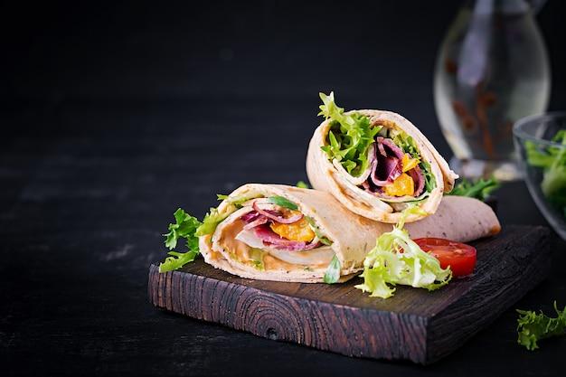 Świeża Tortilla Zawija Się Z Szynką Wołową I świeżymi Warzywami Na Desce. Burrito Z Wołowiną. Kuchnia Meksykańska. Skopiuj Miejsce Premium Zdjęcia