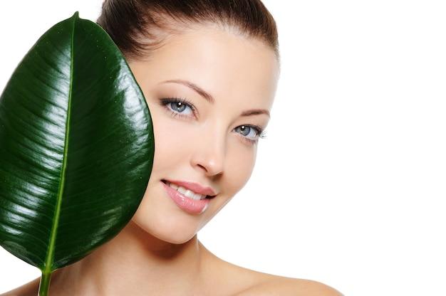 Świeża twarz kobiety z wesołym uśmiechem i dużym zielonym liściem na białych deseniach Darmowe Zdjęcia