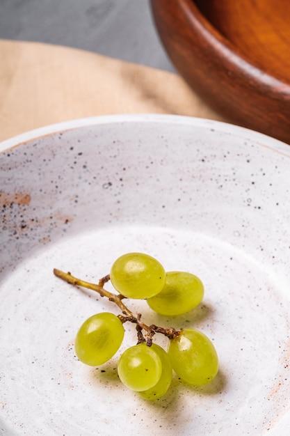 Świeże, Dojrzałe Białe Jagody Winogronowe W Drewnianej Misce Z Płytą Na Lniany Obrus, Beton, Kąt Widzenia Makro Premium Zdjęcia