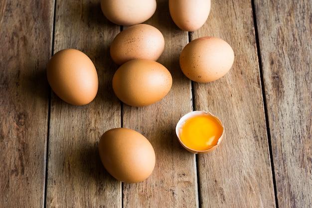 Świeże Jaja Organiczne Rozrzucone Na Drewnianym Stole Kuchennym, Popękana Skorupa Z Otwartym żółtkiem Premium Zdjęcia