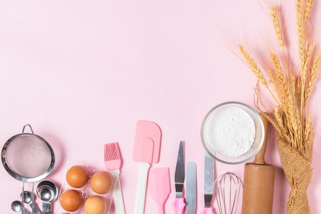 Świeże Jajka I Mąka Tortowa Z Naczynia Kuchenne Do Wypieków Na Różowym Tle, Przygotować Się Do Koncepcji Ciasta I Piekarni Premium Zdjęcia