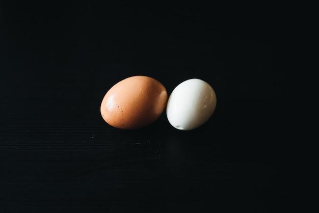 Świeże Jajka Na Twardo Ze Skorupką Obok Na Czarnej Desce (selektywne Ustawianie Ostrości) Premium Zdjęcia