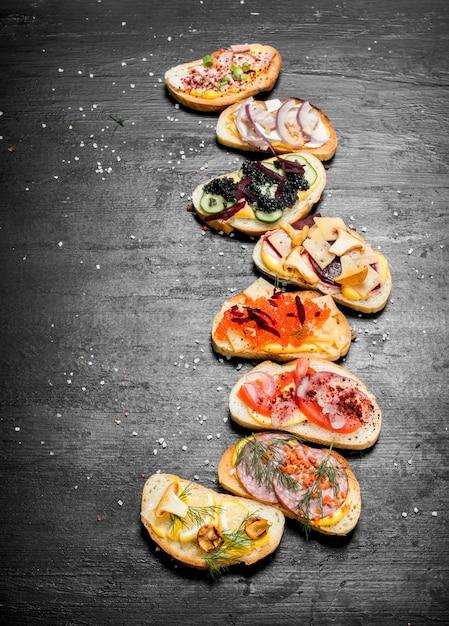 Świeże Kanapki Z Owoców Morza Z łososiem, Kawiorem, Warzywami Z Boczku Na Czarnej Tablicy. Premium Zdjęcia