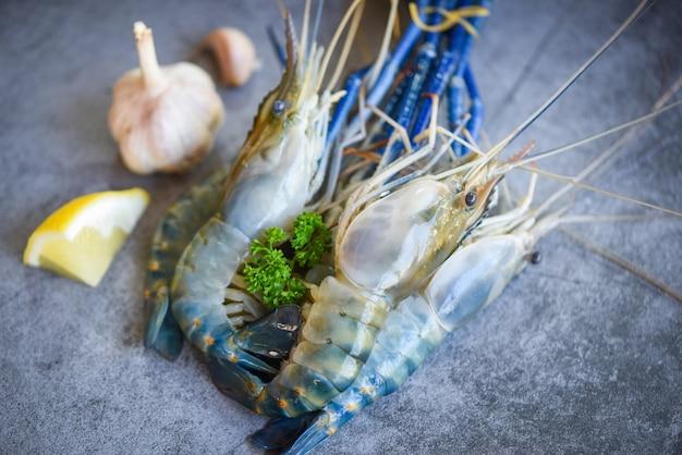Świeże Krewetki Krewetkowe Z Przyprawami Czosnek Cytrynowy Do Gotowania Na Ciemnym Tle W Restauracji Z Owocami Morza - Surowe Krewetki Premium Zdjęcia