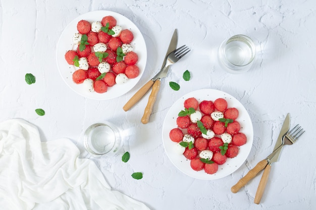 Świeże Letnie Sałatki Z Arbuzem, Mini Mozzarellą, Liśćmi Mięty I Nasionami Chia. Pojęcie Zdrowej Diety Wegetariańskiej Premium Zdjęcia