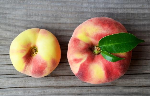 Świeże Organiczne Chińskie Płaskie Brzoskwinie Z Liśćmi Premium Zdjęcia