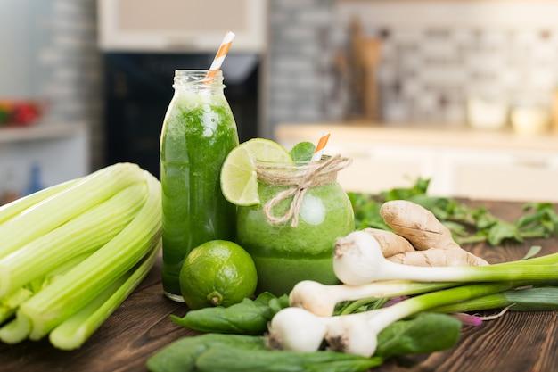 Świeże Owoce I Butelka Z Zielonymi Koktajlami Na Kuchennym Stole Premium Zdjęcia